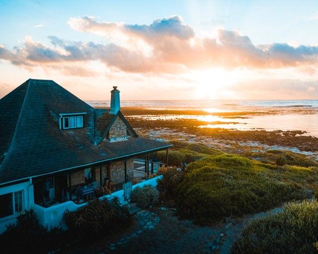 Sie sehen ein Haus am Meer mit Sonnenaufgang