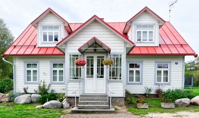 Sie sehen ein Haus mit grünem Vorgarten und rotem Dach