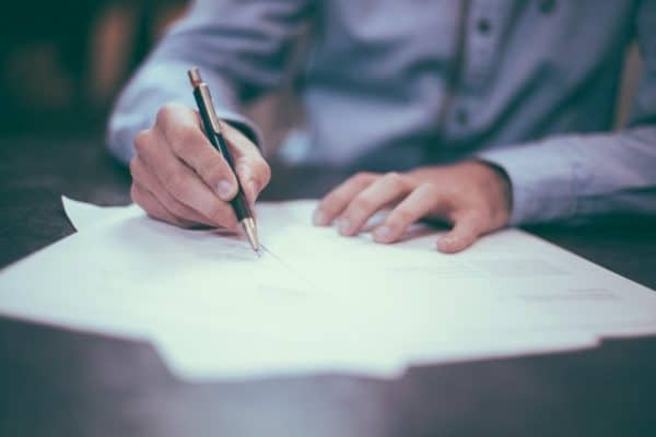 Sie sehen einen Mann bei Vertragsunterzeichnung mit Stift