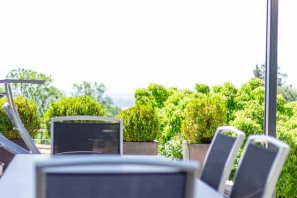 Sie sehen den Blick ins Grüne an einem Tisch mit Stühlen