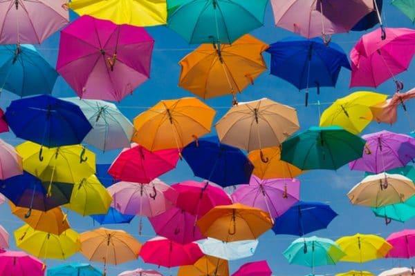 Sie sehen Schirme, die den Schutz durch eine Immobilienversicherung symbolisieren