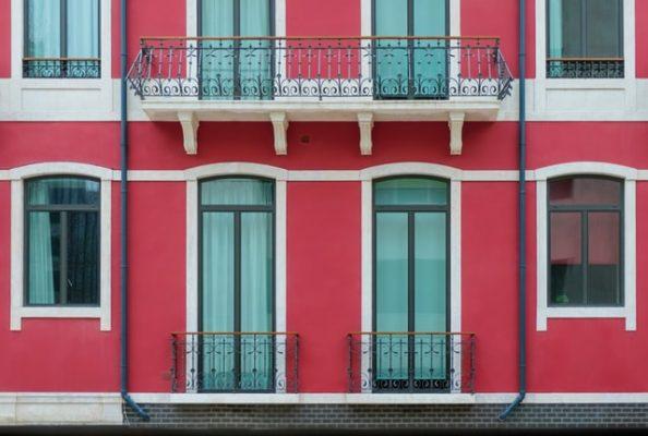 Sie sehen eine Wohnung mit roter Fassade und Balkon